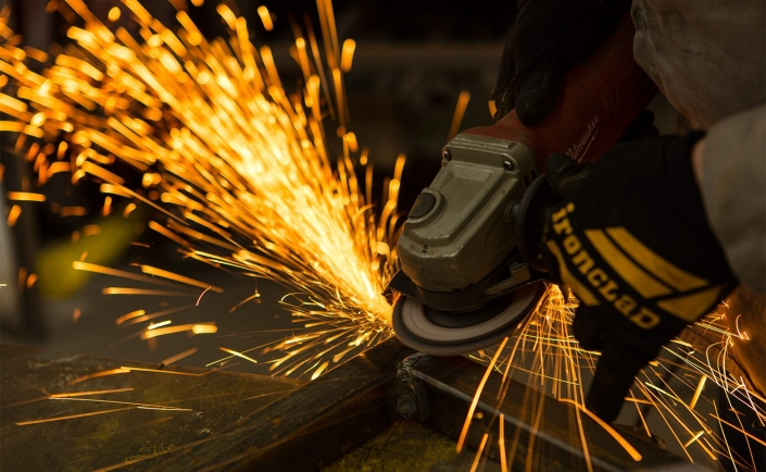 Manufacturing photographer - industrial grinder sparks worker safety gloves