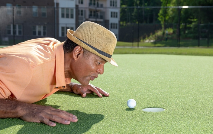 Senior retired golfer blowing ball into cup