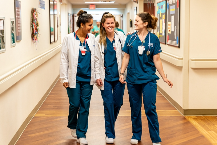 Healthcare Lifestyle Photography - Nurses in hospital hallway laughing and smiling