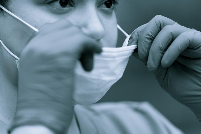 Healthcare nurse putting on mask