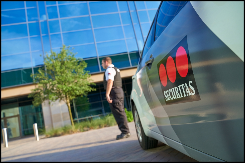 Corporate photography of security expert with branded car on location