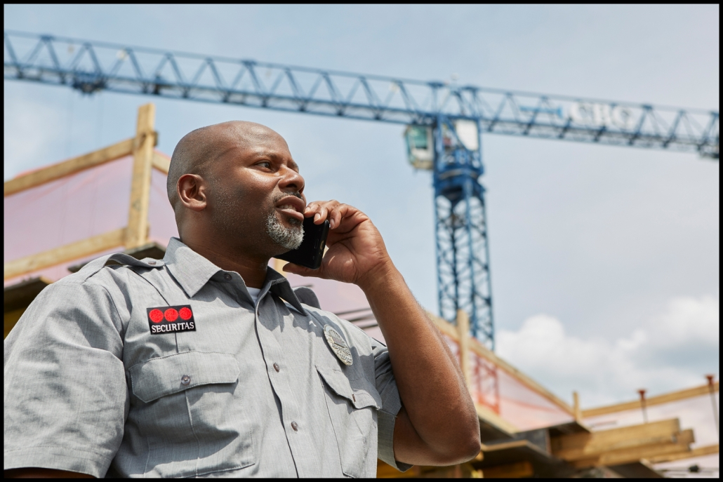 Corporate photography of security expert on location at a construction site with crane