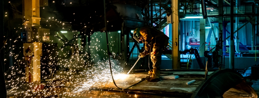 Industrial Photography - Worker cutting metal tank