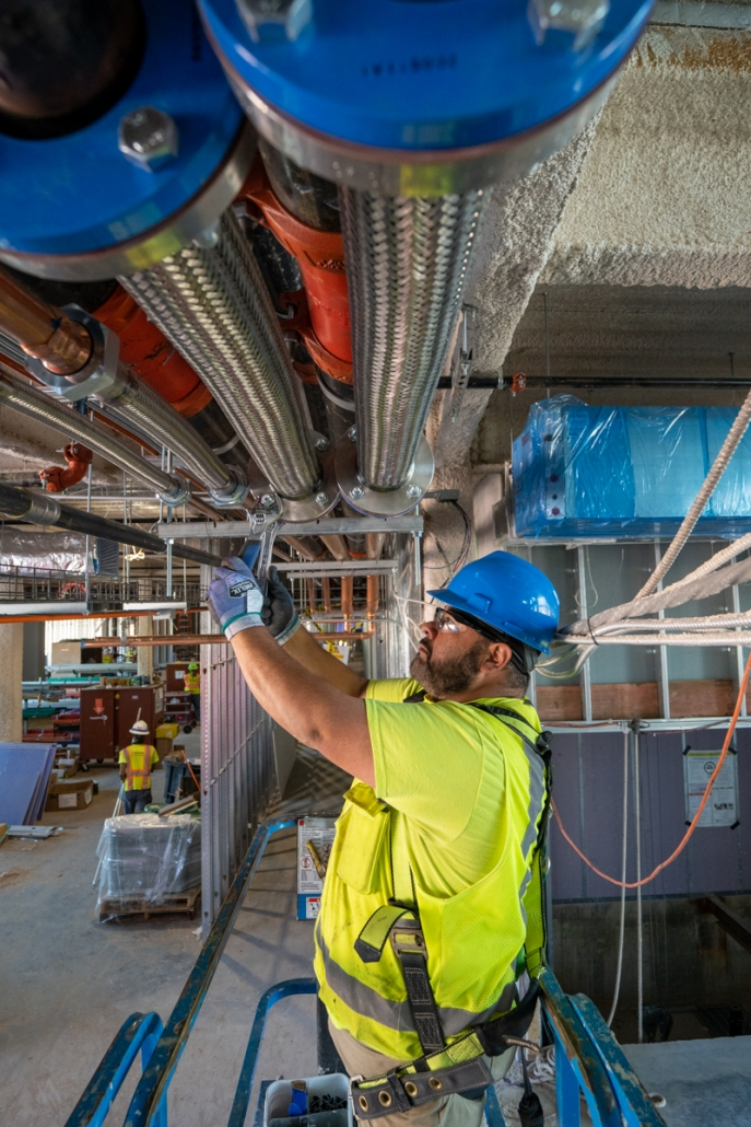 Michael LoBiondo Photography - Worker installing cooling pipe for HVAC